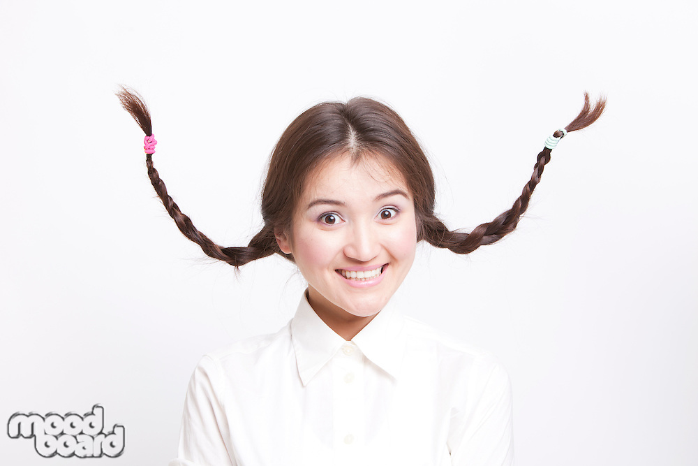 Portrait of young Asian woman with braids curling upwards against white background
