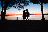 A man and woman kissing on a park bench at sunset.  County Park, San Juan Island, Washington, USA.