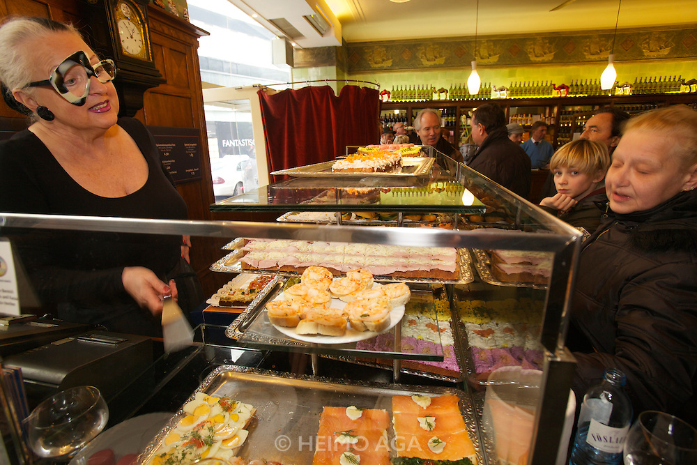 Vienna. Zum schwarzen Kameel. Erna Lenhardt serving to clients at the sandwich counter.