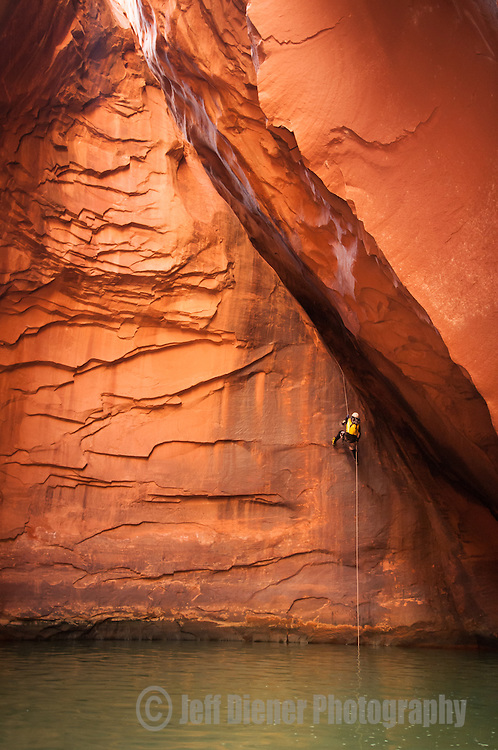 A young woman rappells into a glowing cavern while canyoneering in Anasazi Canyon at Lake Powell, Utah.