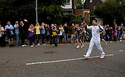 UK, July 7 2012: Paul Draper carries the Olympic Torch in Moulsham Street towards Oaklands park on Saturday 7th July 2012. Copyright 2012 Peter Horrell.