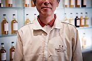 Yamazaki, November 22 2011 - Suntory whisky distillery in Yamazaki, Japan. An employee of the ditillery posing in front of bottles on display.