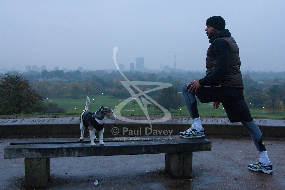 Primrose Hill, London, October 30th. As mist shrouds London's skline, fitness fanatics run and work out on Primrose Hill. Pictured: Ex Nottingham Forest and Sheffield Wednesday and Ghanaian international footballer Junior Agogo exercises on Primrose Hill, watched by his dog.