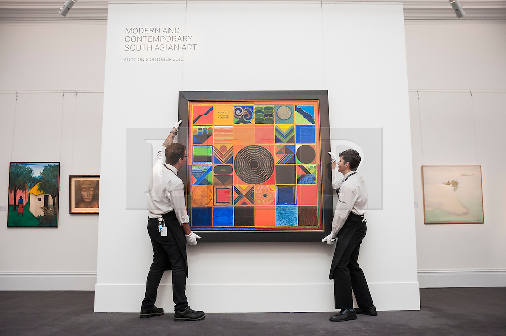 "© Licensed to London News Pictures. 02/10/2015. London, UK. Sotheby's technicians help to hang ""Bhartiya Samaroh"" by Sayed Haider Raza (est. £500k - 700k) at the preview of Indian and Islamic Art Week at Sotheby's which runs from 2 to 7 October.  Photo credit : Stephen Chung/LNP"
