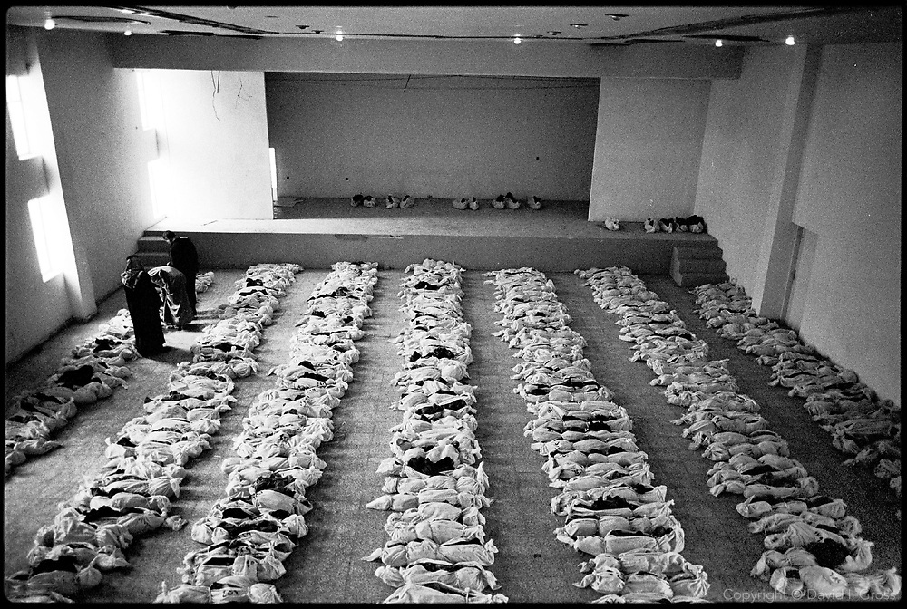 Bones in shrouds fill the gymnasium of the local sports center in Al-Musayab, Iraq, now the home of an Iraqi human rights organization which is overseeing the exhumations of bodies from local mass graves. People come from all over to check the clothing and ID cards of the bodies, looking for relatives.