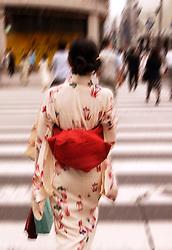 Motion blur image of woman wearing  kimono crossing street in central Tokyo Japan