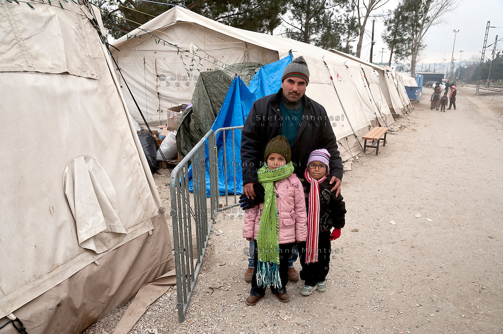 Dad with daughters refugees of Baghdad, Iraq, waiting to cross the door of the Greek-Macedonian border , where they will be transporded by train to the Serbian border. 9 Febraury 2016<br /> Hundreds of refugees arrive at Idomeni and cross the border between Greece and Macedonian on their journey to North Europe.