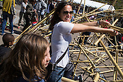 A mother and child add pieces to a bamboo and zip-tie play piece at Sub Rosa's sustaninable play booth.