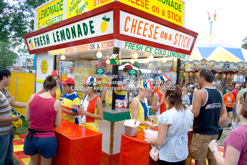 Customers buying lemonade and cheese on a stick at a garish concession stand. Minnesota State Fair St Paul Minnesota MN USA