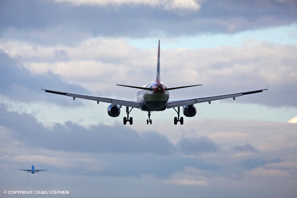 A plane landing and one taking off at Edinburgh airport, Scotland, UK