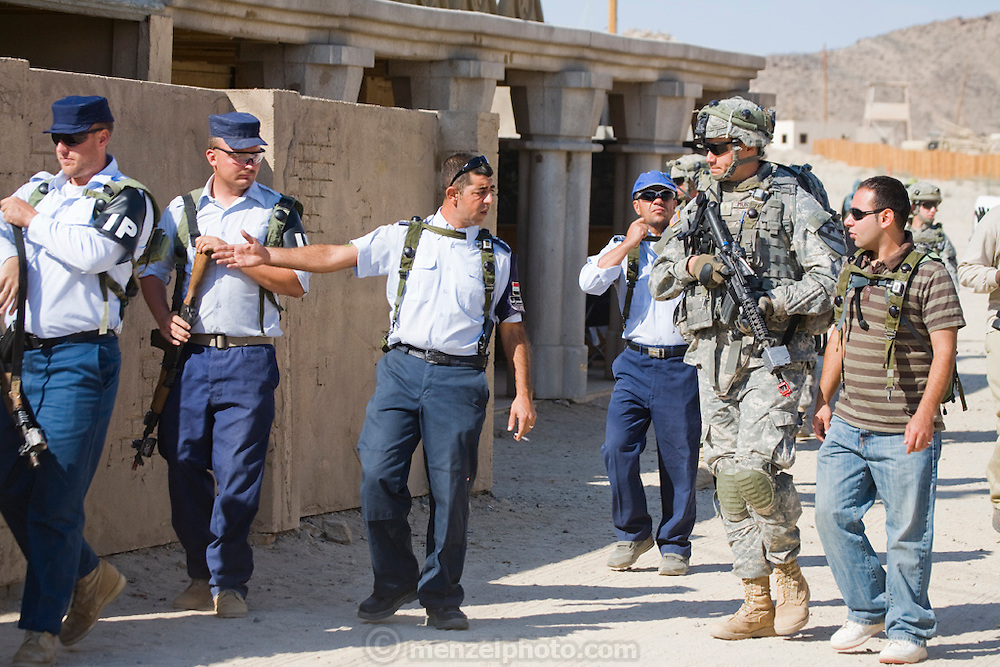 Iraqi police officers and their U.S counterparts patrol a street in a fabricated Iraqi village at Fort Irwin, California. The sets are used for combat training exercises before the troops deploy to Iraq.