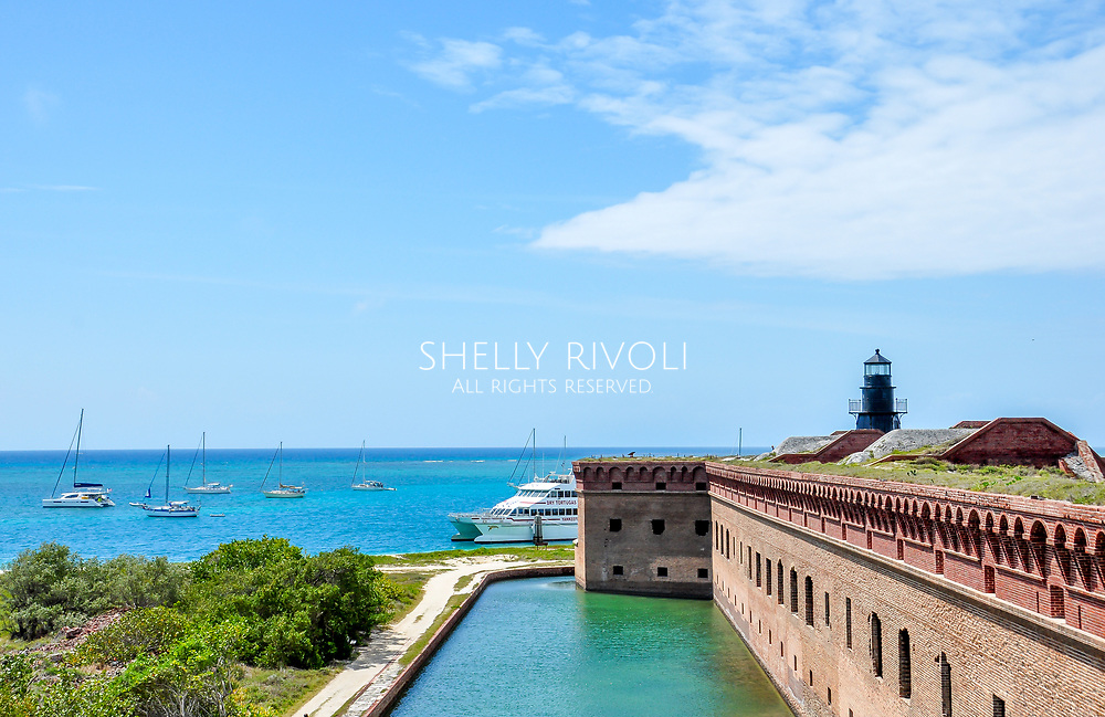 View from Fort Jefferson roof with brick wall, water, sailboats and lighthouse at Dry Tortugas National Park. The Fort Jefferson historic military site can be visited on a day trip from Key West, Florida.
