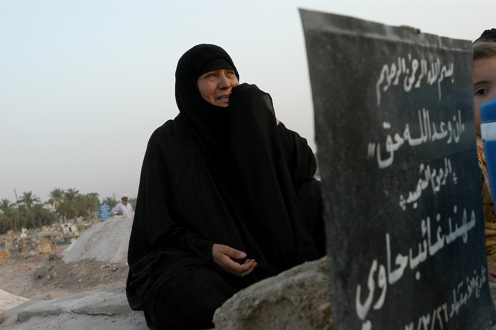 A woman weeps for a family member killed during the war in a cemetary for people who can't afford or are unable to bury the dead in the Najaf sacred burial ground..Basra, Iraq. 20 May 2003..Photo © J.B. Russell