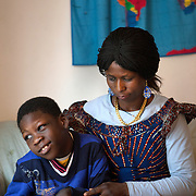 """Atlanta, Georgia/Central Africa Republic Refugee/Nestorine Lakas, 27, holds her son Eric who has cerebral palsy, at their apartment in Atlanta. Nestorine arrived in the U.S. in 2010 with her two young children from the Central African Republic. Her son, who is now 7 years old, suffers from severe cerebral palsy and requires a wheelchair and specialized healthcare. At the IRC in Atlanta, Nestorine is part of the Temporary Assistance for Needy Families (TANF) program where she is learning English, job skills and basic computer literacy so she can support her family as a single mom and learn how to manage her son's health needs. Unfortunately the father of Nestorine's children was not able to come to the U.S. with her, so she cares for her children and dreams of reuniting with him someday. Nestorine believes what makes her successful is ?working hard and overcoming challenges?. """"There was a war in my country and I fled to Cameroon. I was pregnant with my older son and gave birth along the way. When I fled I was alone. When I got to the camp I found my husbands name on a sign at the camp and we were reunited. My daughter Carol was born in Cameroon."""" Because of her son's disability, Nestorine got a humanitarian visa with the help of UNHCR. """"I am very happy to be here because they helped me a lot with my child. If I had stayed in CAR there isn't the healthcare that I have here. I am very thankful. The reason my child is still alive because I came as a refugee. Maybe the child would not have had any hope to walk. I hope one day he might walk.""""."""