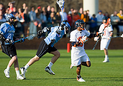 Virginia midfielder Will Barrow (23) runs past Johns Hopkins attackman Michael Doneger (14).  The #2 ranked Virginia Cavaliers defeated the #6 ranked Johns Hopkins Blue Jays 13-12 in overtime at the University of Virginia's Klockner Stadium in Charlottesville, VA on March 22, 2008.  The loss, in front of a record UVA crowd of 7,500, was the third consecutive overtime defeat for Hopkins, the defending national champions.