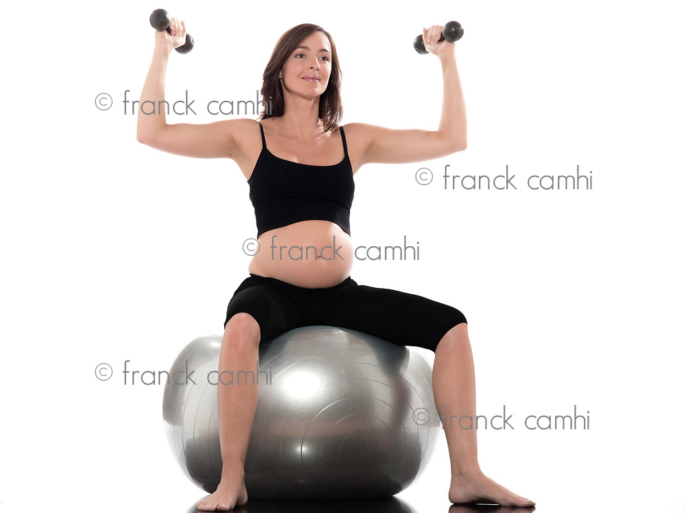 one Pregnant Woman Workout weight training pilates sitting on swiss ball isolated studio on white background