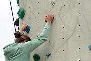 Young teen girl climbs up an artificial climbing wall close up of the hands