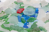 A plate full of beach glass shows the variety of blues, greens, red and whites of ocean-tumbled glass.