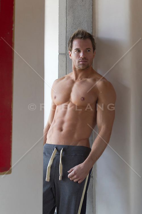 very good looking man in sweatpants leaning against a wall