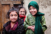 Kabul: Young girls wait for their parents  who wait in line at a UNHCR  distribution event at Tamir Mill Bus site...UNHCR distributes charcoal and NFI's to registered IDP's at one of Kabul's Informal Settlement Sites in the city centre...57 families eek out a living in a dilapidated warehouse building owned by the Ministry of Transportation. The site originally served as a storage facility for the national bus company...Tajik and Pashtun families live side by side without any major conflict. Over 70% of the families are returnees from the period 2002-2004 who are unable to achieve sustainable reintegration in their places of origin and subsequently drifted to Kabul City in search of work...There is a nearby school which is accessible to the children but the poor economic circumstances of the many families oblige them to send their children out to work. low levels of literacy, particularly amongst the women, limit their access to employment other than the lowest paid daily wage labor...Afghanistan. /UNHCR/Jason Tanner/February 2011