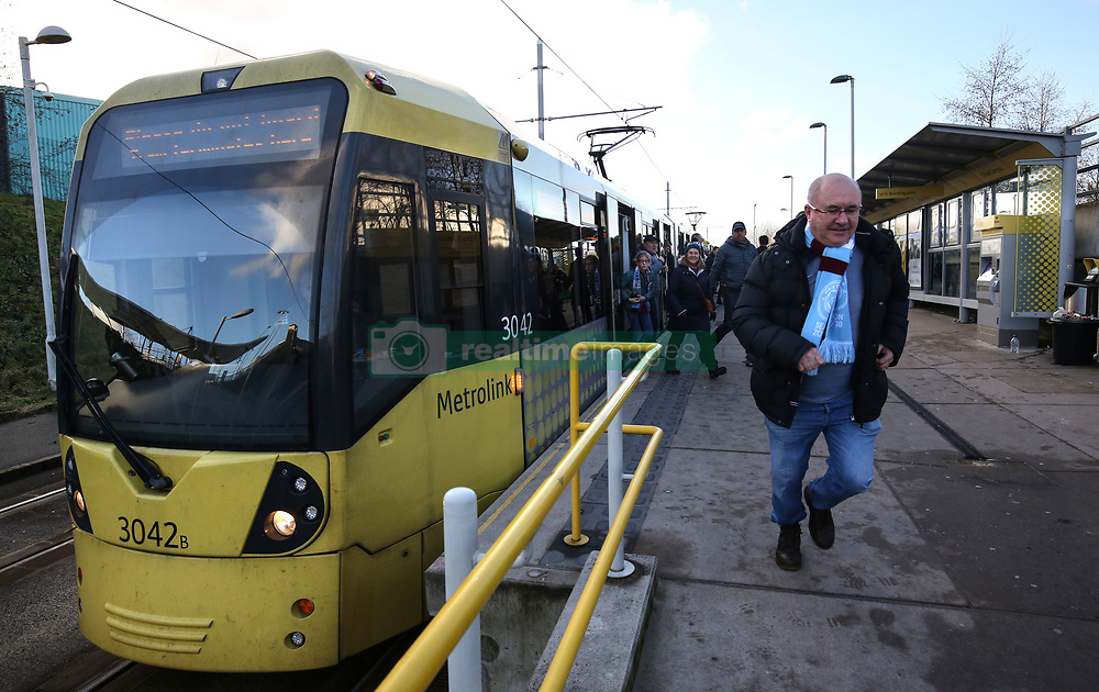 6 January 2018 - FA Cup (3rd Round) Football - Manchester City v Burnley - A fan runs off the tram to get to the ground - Photo: Charlotte Wilson / Offside