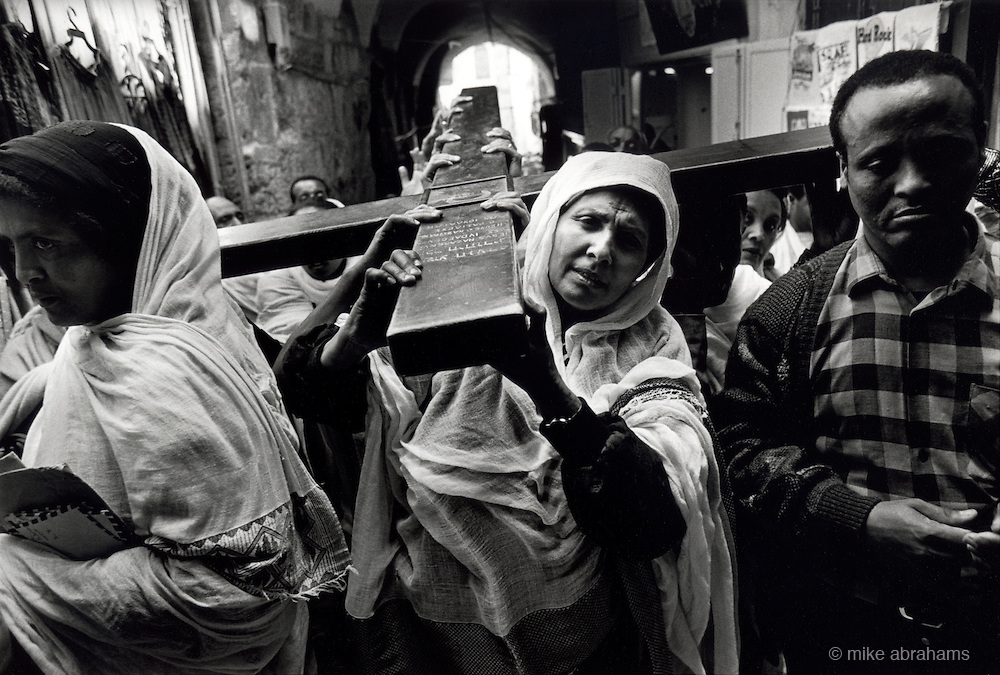 Pilgrims walk up the Via Dolorosa marking the Stations of the Cross during Holy Week. Jerusalem, Israel