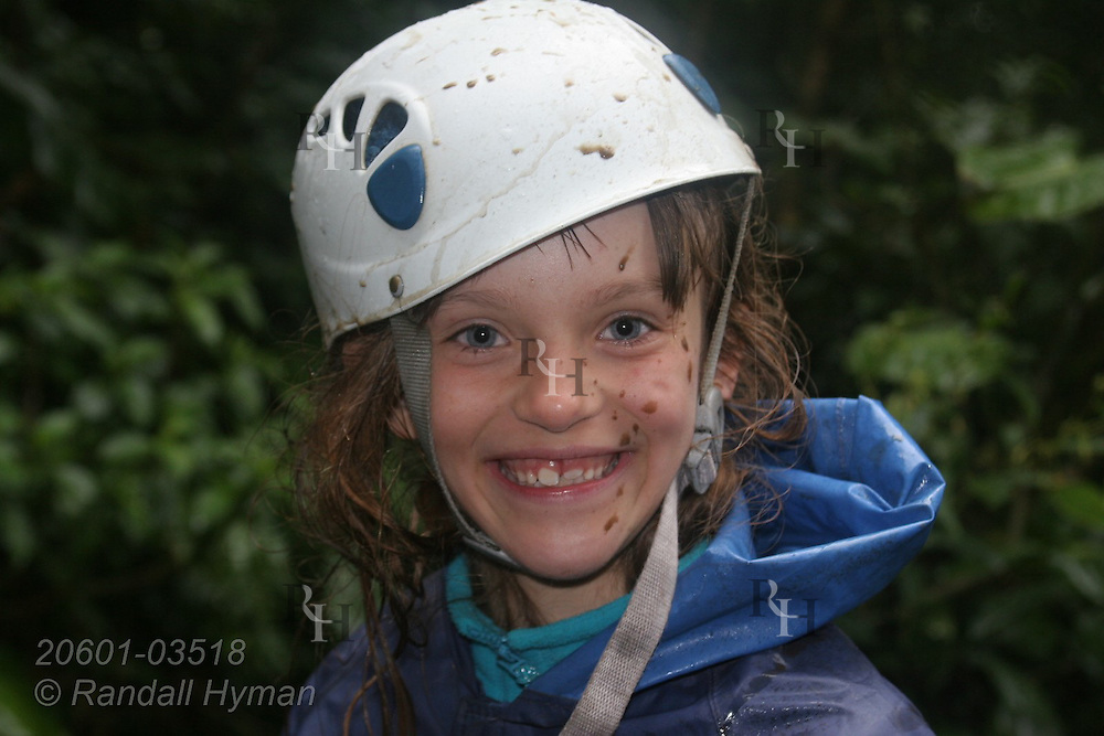 Ecoteach girl Caitlin Seibel (age 9) smiles with rust-spattered face during rainy zipline adventure through the Monteverde cloud forest on Sky Trek cables; Monteverde, Costa Rica.