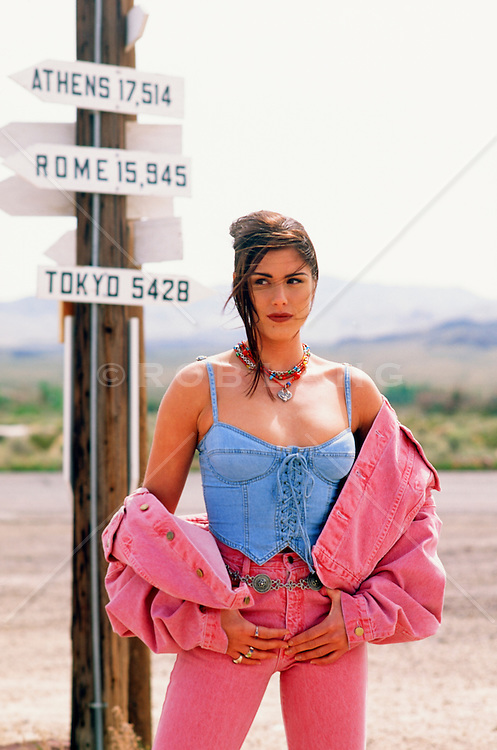 woman in pink and blue denim standing in the desert near a directional sign