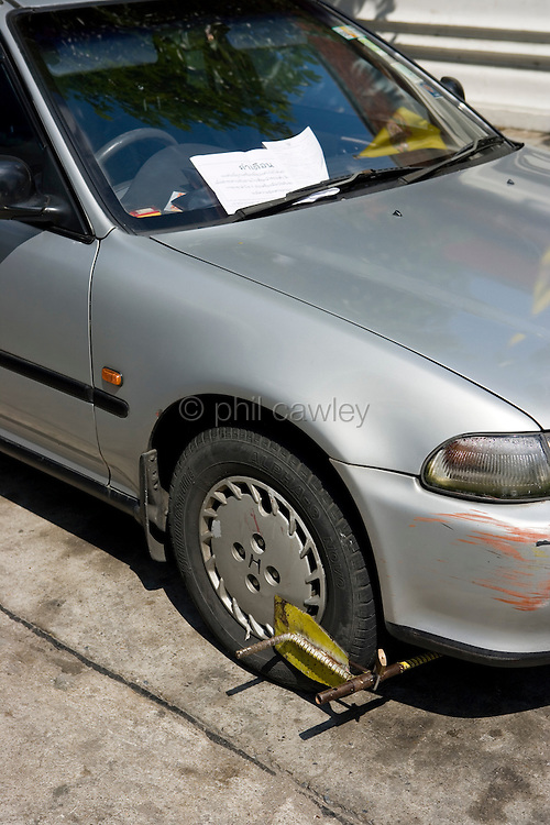 Car with a parking ticket and wheel clamp, Thailand Asia