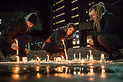 WASHINGTON, USA - February 11: Lee Elliott (L) from Chapel Hill, N.C., Tera Schmitt (C) from Durham, N.C., and Peter Bonsai from Durham, N.C. relight candles in a memorial at a vigil for Deah Shaddy Barakat, Yusor Abu-Salha, and Razan Abu-Salha who were killed in their home the night before in Chapel Hill on February 11, 2015. Samuel Corum / Anadolu Agency