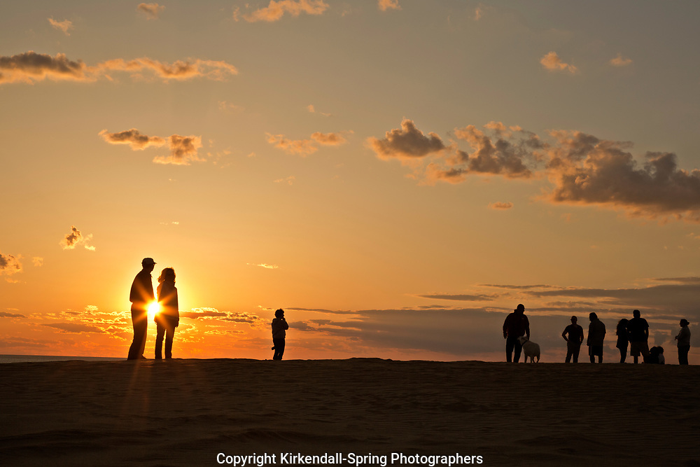 NC01427-00...NORTH CAROLINA - Watching the sunset from a tall sand dune, a popular activity at Jockey's Ridge State Park on the Outer Banks at Nags Head.