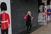 A woman smokes a cigarette near images of Queen Elizabeth II, a guardsman and Superman, on 3rd February 2017, in London, England.