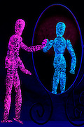 Glowing pink manequin looks at its blue reflection in a mirror.Black light