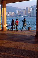 A woman photographs the city skyline from the Promenade in Kowloon, Hong Kong, China.
