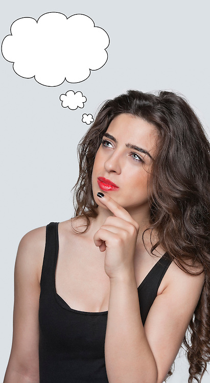 Thoughtful young woman looking at speech bubble with hand on chin over gray background