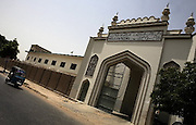 An auto rickshaw passes in front of the main gate of the Darul Uloom Naeemia in Karachi, Pakistan.