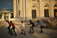 Port-au-Prince, HAITI, 22/03/2011: One year after the massive earthquake hit Haiti's capital, people try to recover their quotidian life, in the middle of a destructed city. Inline skaters riding beside the cathedral ruins.  (photo: Caio Guatelli)