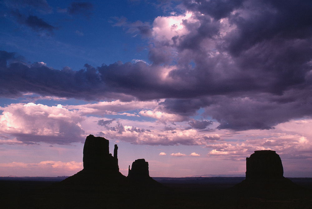 The buttes of Monument Valley, Utah, are silhouetted at sunrise.
