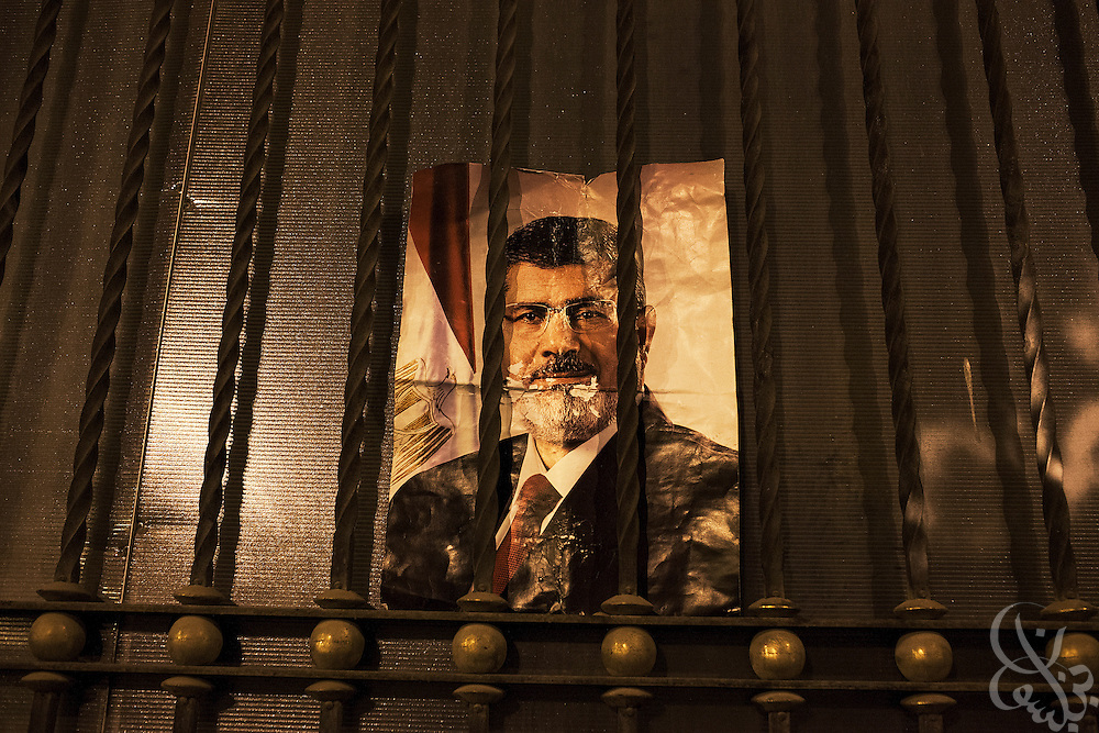 A poster of deposed Egyptian President Mohamed Morsi remains on the fence outside the Ministry of Investment building following a day of marches in the area by his supporters Friday July 19, 2013 in the Nasr City area of Cairo, Egypt. Three weeks after the military removed Morsi from power, the ex-leader has yet to be seen or heard from, and remains confined at an undisclosed location by the military.