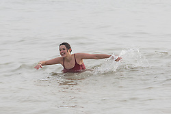 © Licensed to London News Pictures. 18/12/2016. Brighton, UK. A young woman braves the cold water to go for a swim in the sea as mild weather is hitting Brighton and the South Coast. Photo credit: Hugo Michiels/LNP
