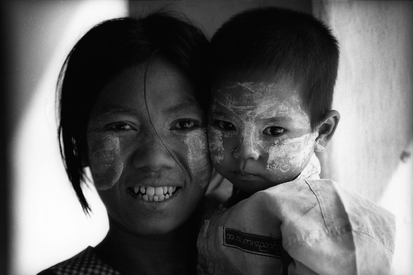 A young teenage mother stands for a portrait holding her son. Yangon, Myanmar.