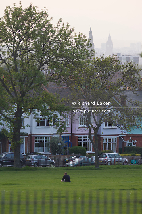 Tranquil moment for a lone south London park dweller with a hazy cityscape in the distance.