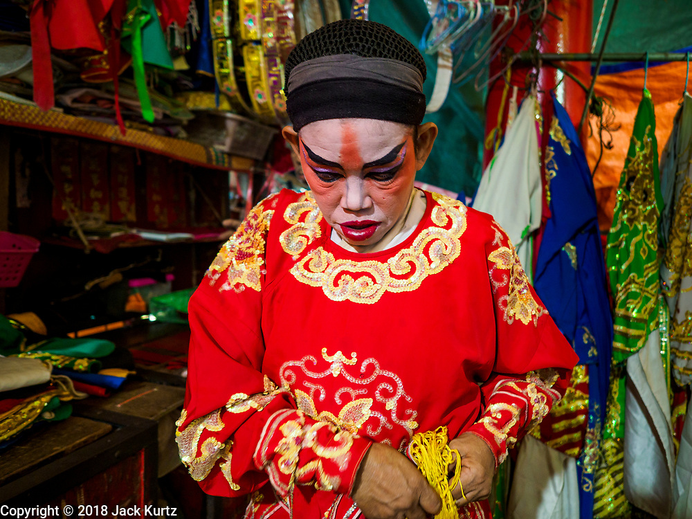 17 OCTOBER 2018 - BANGKOK, THAILAND: A man puts on his costume before the Chinese opera on the last night of the Vegetarian Festival at Chit Sia Ma Shrine in Bangkok's Chinatown. The Vegetarian Festival, also called the Nine Emperor Gods Festival, is a nine-day Taoist celebration beginning on the eve of 9th lunar month of the Chinese calendar. Traditional Chinese operas, called Ngiew in Thailand, are sponsored at many Chinese shrines and temples during the Vegetarian Festival.    PHOTO BY JACK KURTZ