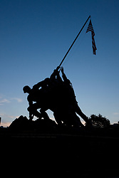 """The Marine Corps War Memorial is a military memorial statue located near the Arlington National Cemetery and the Netherlands Carillon in Rosslyn, Virginia, United States. The memorial is dedicated to all personnel of the United States Marine Corps (USMC) who have died in the defense of their country since 1775. Its design was based on the iconic photo from the Battle of Iwo Jima..In 1951, work commenced on creating a cast bronze memorial based on the photo, with the figures 10 meters (32 feet) tall and the flagpole 20 meters (60 feet) long. The granite base of the memorial bears two inscriptions:.    * """"In honor and memory of the men of the United States Marine Corps who have given their lives to their country since 10 November 1775"""".    * """"Uncommon Valor was a Common Virtue."""" ? a tribute by Admiral Chester Nimitz to the fighting men on Iwo Jima..The location and date of every major Marine Corps engagement up to the present is inscribed around the base of the memorial..The memorial was officially dedicated by President Dwight D. Eisenhower on November 10, 1954, the 179th anniversary of the U.S. Marine Corps..In 1961, President John F. Kennedy issued a proclamation that a U.S. Flag should fly from the memorial 24 hours a day ? one of the few official sites where this is permitted. The current U.S. Flag, however, is not a factually accurate depiction of the flag which was raised over Mount Suribachi, as two stars have since been added for Alaska and Hawaii..The original plaster working model of the statue currently stands in Harlingen, Texas at the Marine Military Academy, a private Marine Corps-inspired youth military academy. The Academy is also the final resting place of Corporal Harlon Block, USMC, one of the Marines immortalized in the iconic image (seen at base of flag). Corporal Block was killed in action on Iwo Jima..The National Iwo Jima Memorial in Newington, Connecticut uses a similar design and is dedicated to the 6,821 US personnel who died in the battle."""