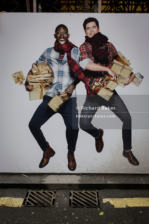 Leaping models advertise clothing retailer H&M above street drain covers in central London.