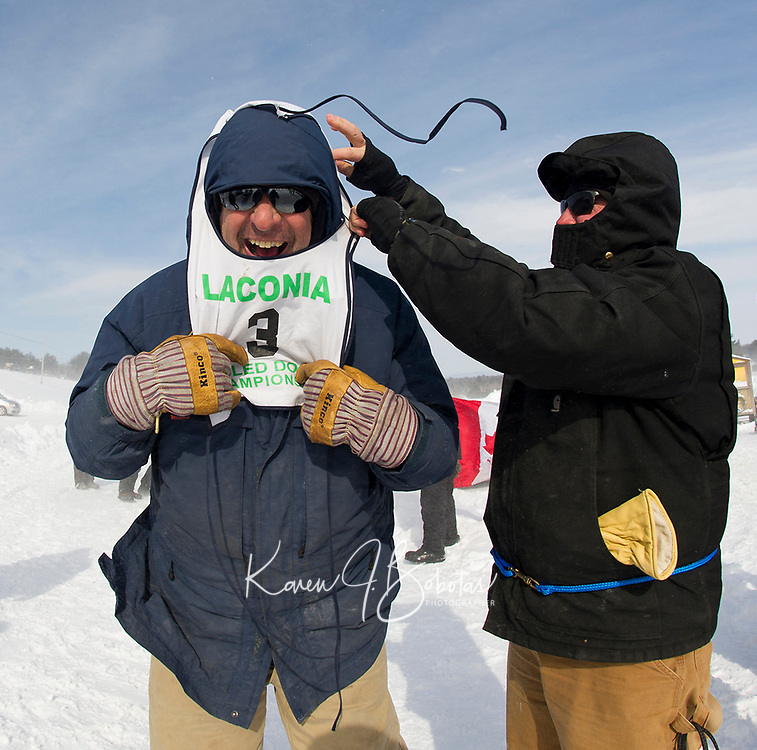 Keith Bryar gets help from Peter Colbath as he puts on his bib for the Open Class race at last years World Championship Sled Dog Races in Laconia.  (Karen Bobotas Photographer)