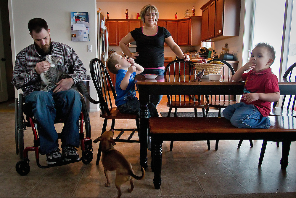 Kyle Mungari and his fiance, Tiana Martinez, relax in their dining room with their sons Brayden, 2, right, and Zachary, 4, during an afternoon snack Wednesday.  Mungari hasn't been able to hold a job since being paralyzed from the waist down following a car accident, but says that it has allowed him more time with his three sons.