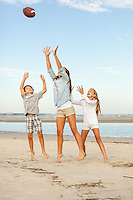 Three siblings try to catch a football while playing on the beach.