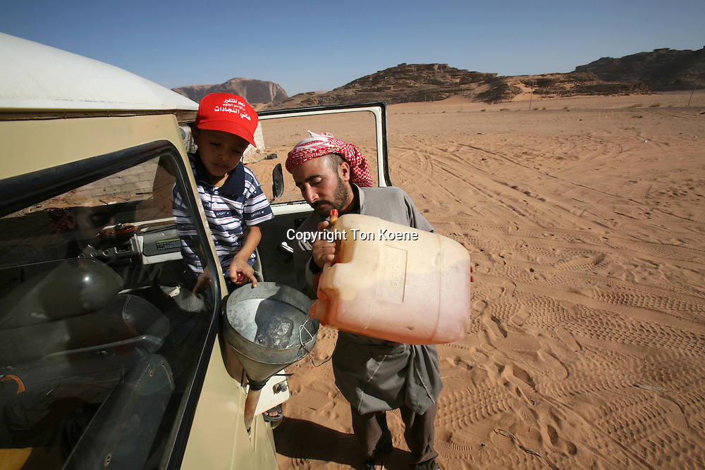 A driver refills his gas tank in the desert, Jordan