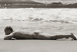 naked man relaxing on the sand by the ocean in East Hampton, NY
